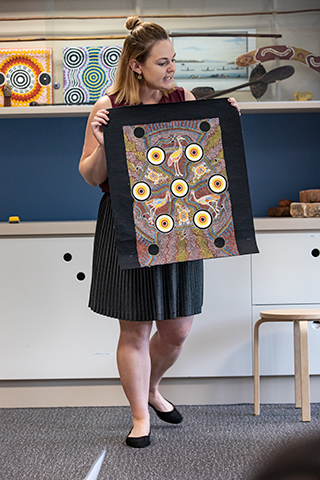 A woman holding an Indigenous artwork