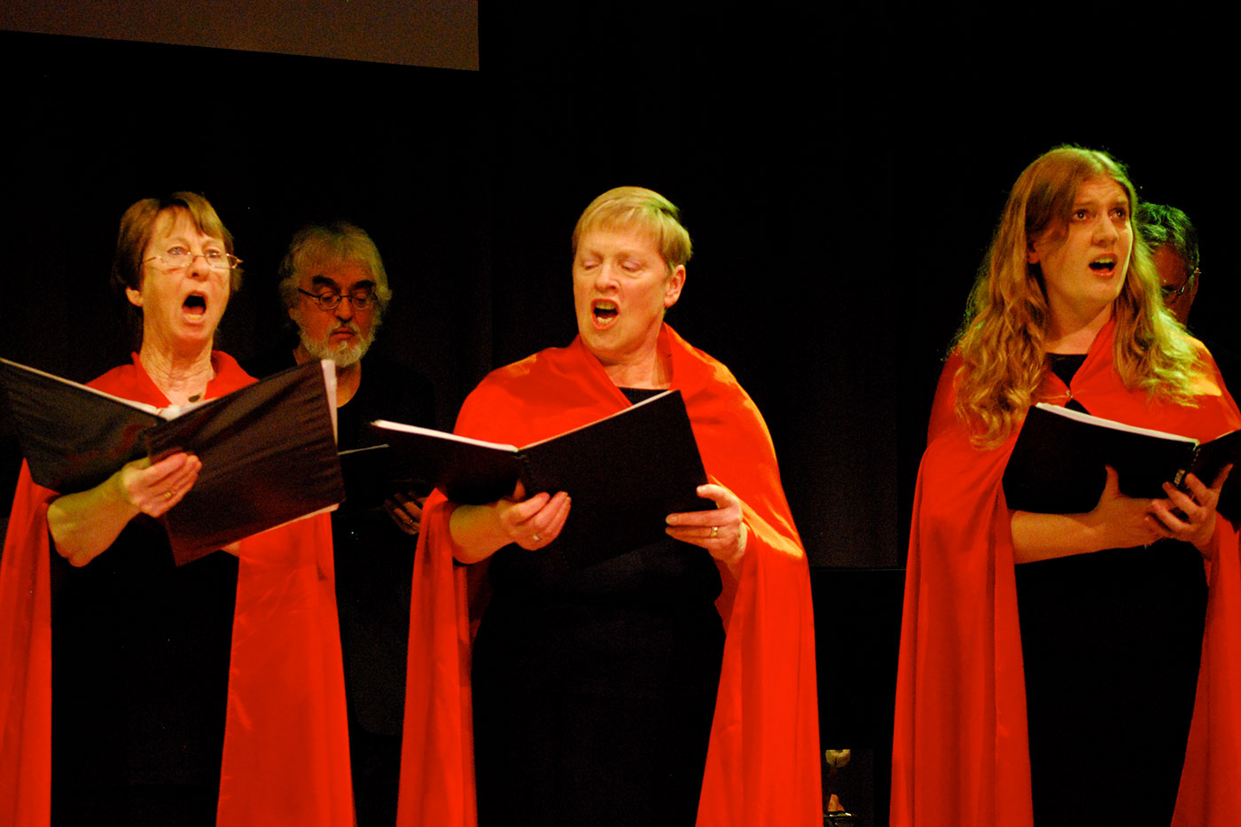 Three women wearing red robes and performing alongside a choir on a stage. - click to view larger image