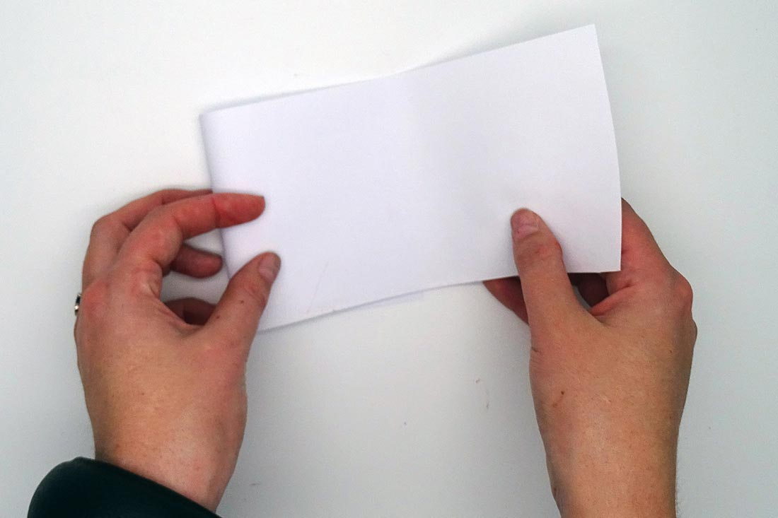 Two hands folding paper into thirds. - click to view larger image