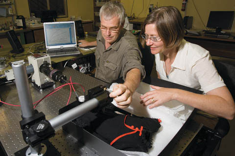 Bruce Ford and Nicki Smith place a small black dress under micro-fading equipment in a museum laboratory.