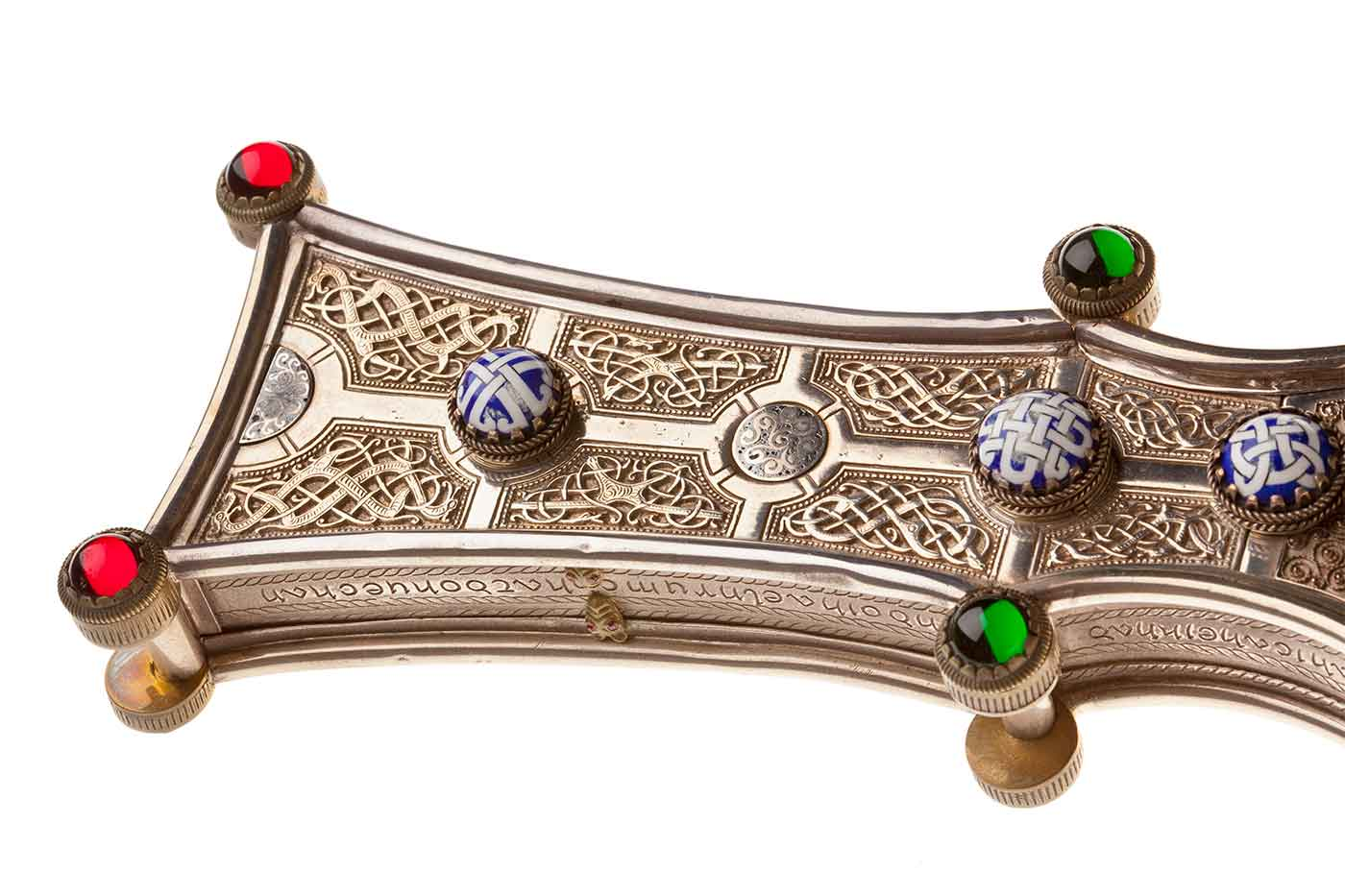 Detail of a golden cross with ornate Celtic design and gemstones. - click to view larger image