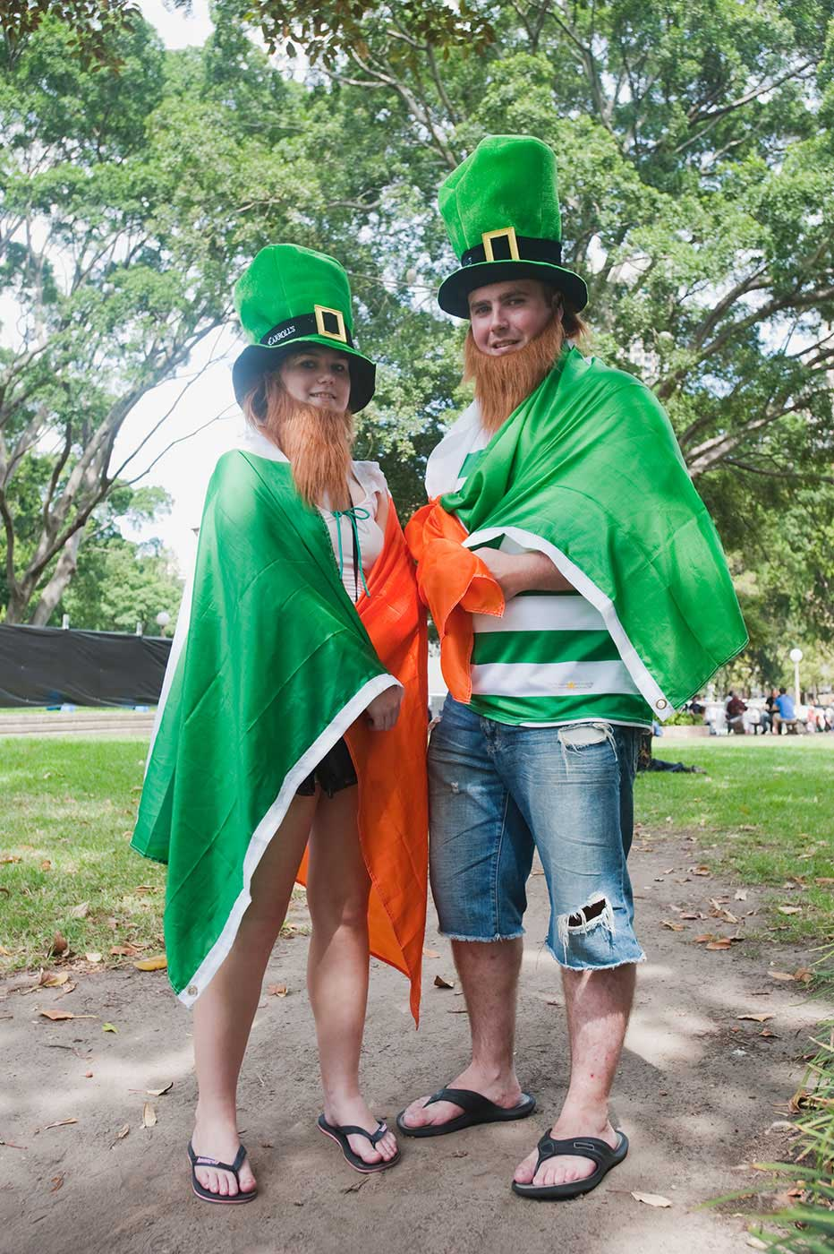 A woman and man draped in the Irish flag and wearing gimmick Irish hats pose for the camera. - click to view larger image