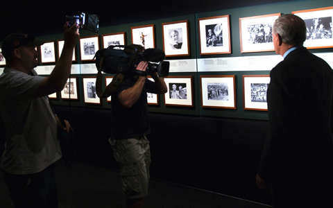 This image of one wall of the exhibition features two parallel rows of framed black and white photographs that stretch across the image horizontally from edge to edge. On the right side of the image Reg Gasnier has his back to the camera and is facing the photographs. A TV camera man faces him with a camera on his shoulder. Next to him another man holds a portable light pointing towards Reg.