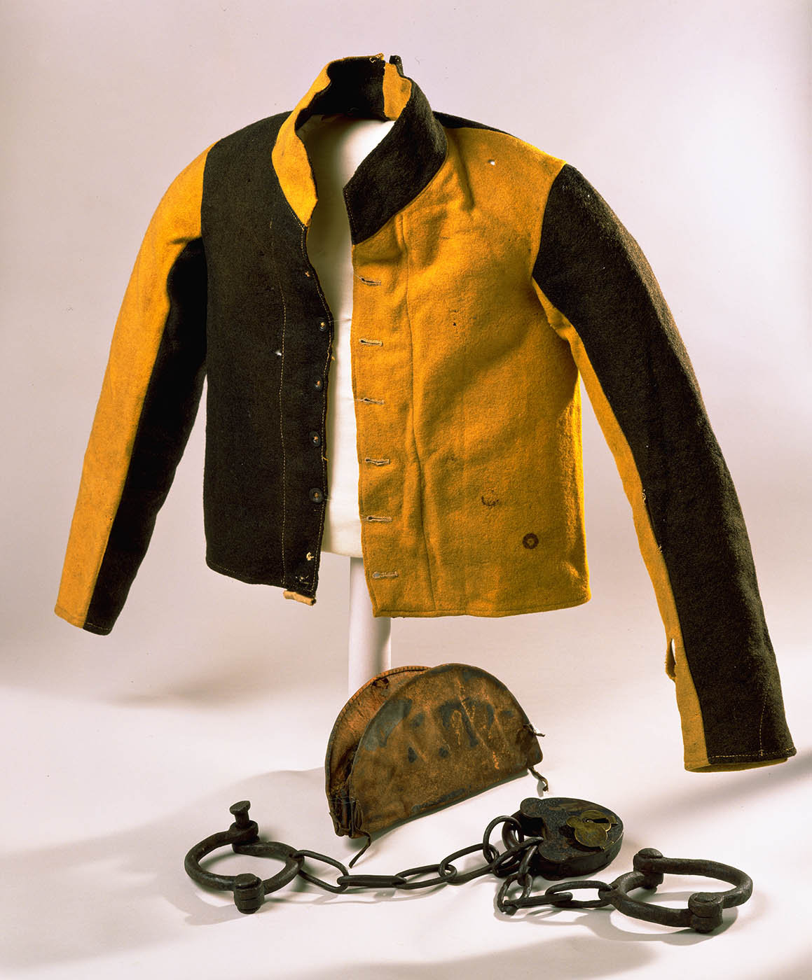 Yellow and black jacket, hand cuffs and pouch on display. - click to view larger image
