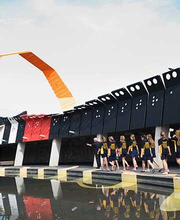 小池塘倚畔在建筑外的一侧;一组穿制服的学生和两名成年人在水池边;背景是黑色和橙色的坡道状建筑延伸到空中。