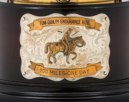 A metal plate on the front of a timber base. It shows an image of a man on horseback and text that reads 'Tom Quilty Endurance Ride, 100 miles, one day'.  - click to view larger image