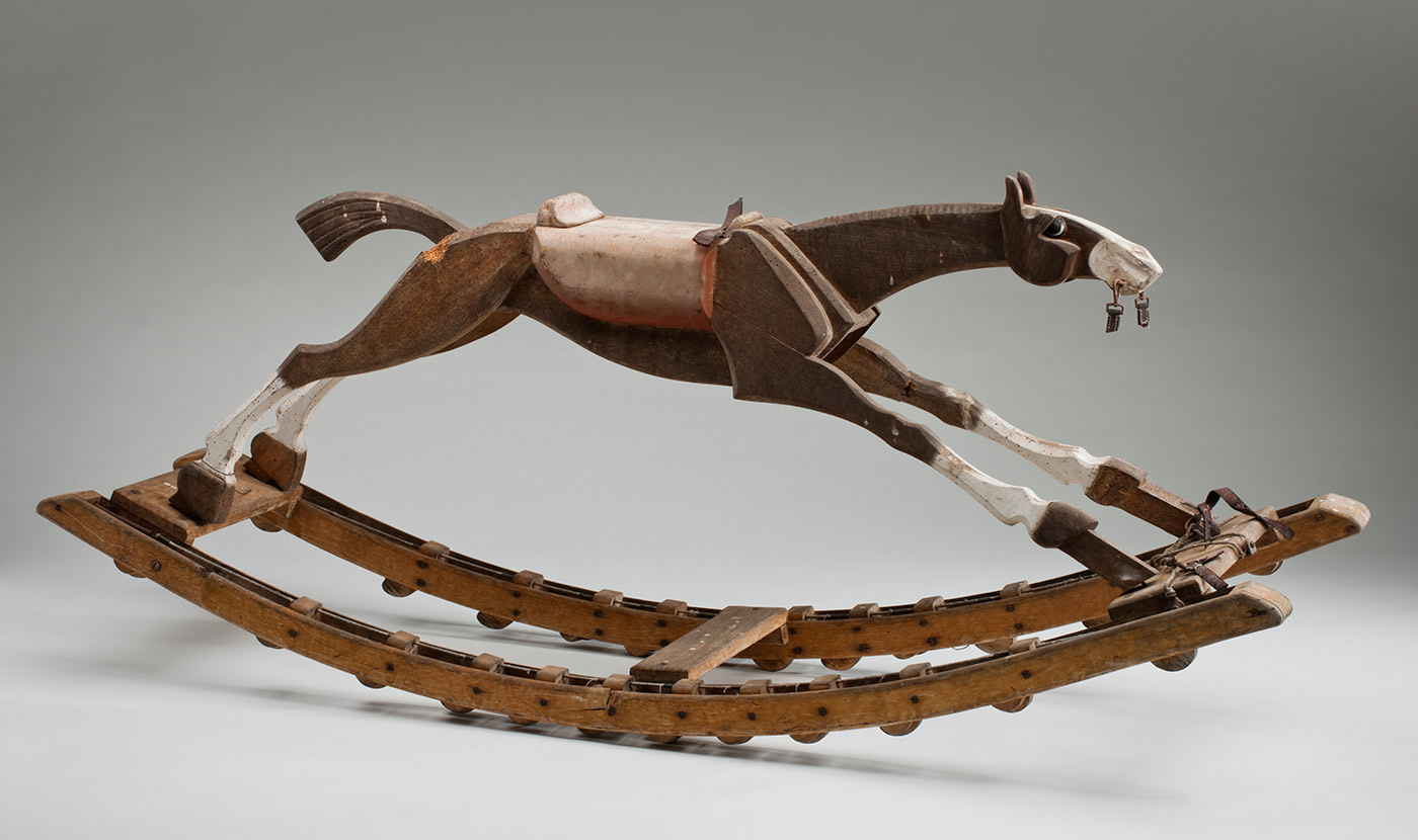 Wooden rocking horse with elliptical wheels.