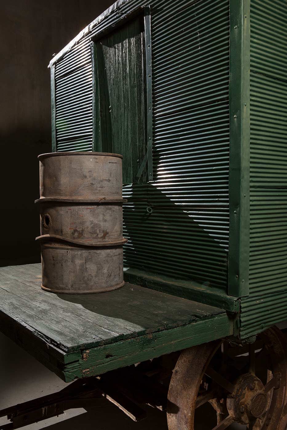 A cook's galley in the form of a metal-clad, timber and iron-framed box raised on wagon wheels. This view is of an outdoor table with drum seated on it, fixed to the rear of the galley. - click to view larger image