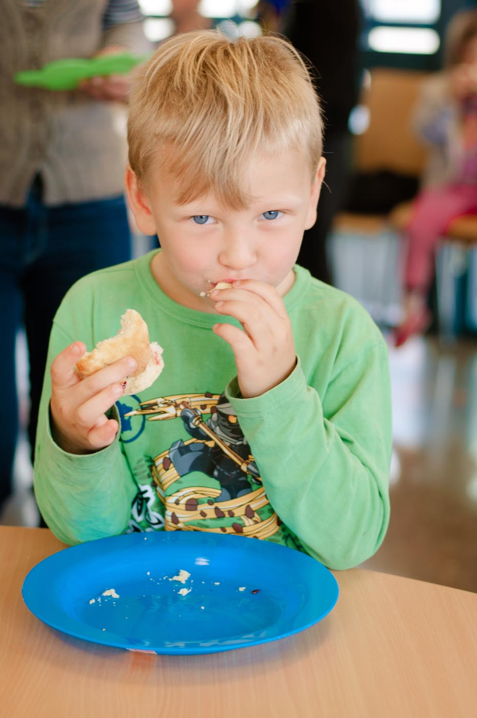 Photo showing a young boy sampling an item of food leaving crumbs on his plate - click to view larger image