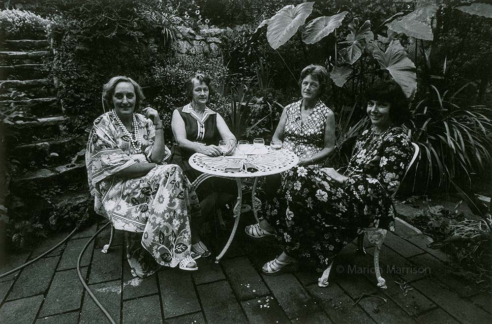 Black and white photo of a group of women sitting at a table in a garden.
