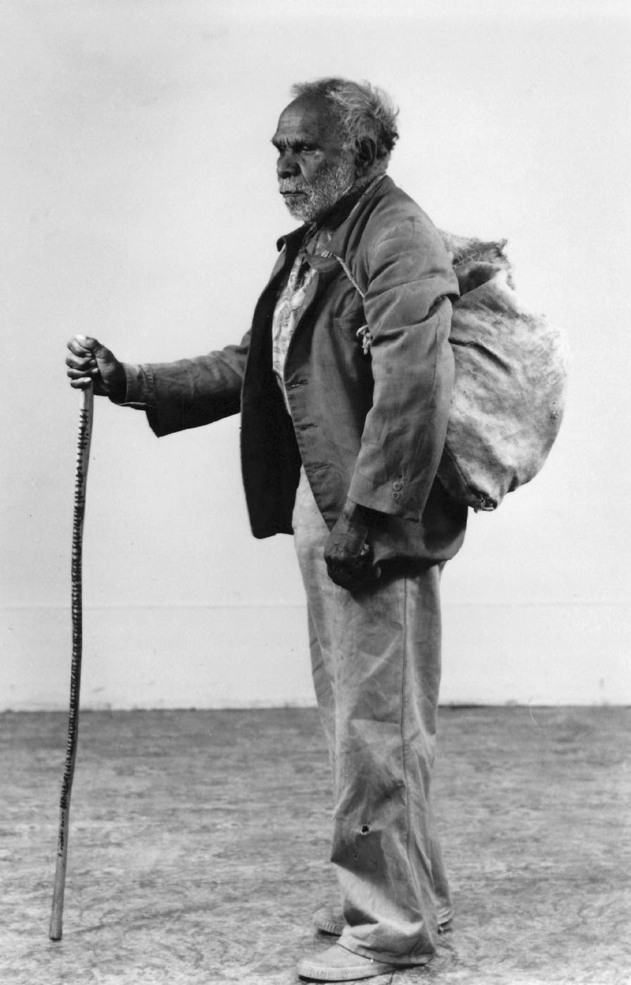 Black and white photo of an elderly man holding a walking stick with markings and carrying a duffel bag. - click to view larger image
