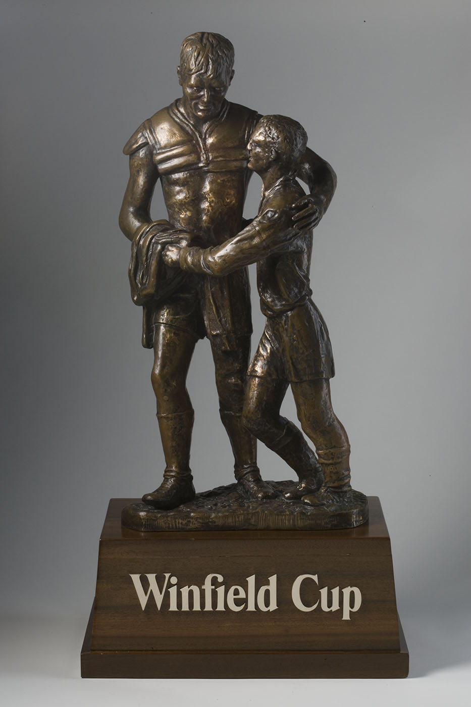 Bronze-coloured trophy with a sculpture of two footballers embracing, atop a base with text: ' Winfield Cup'. - click to view larger image
