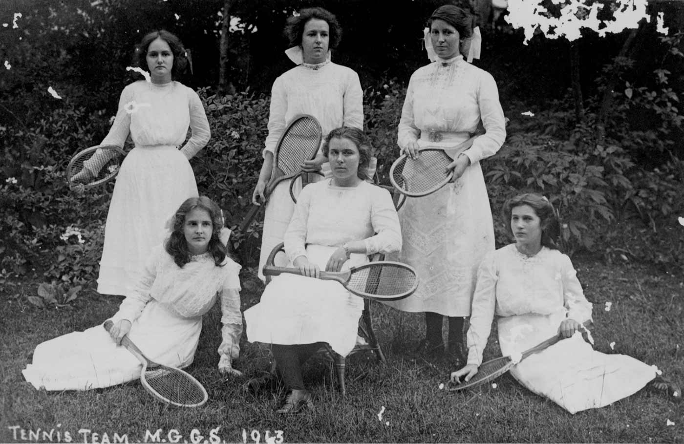 A black and white photo of a group of six women in tennis dresses and holding tennis racquets.