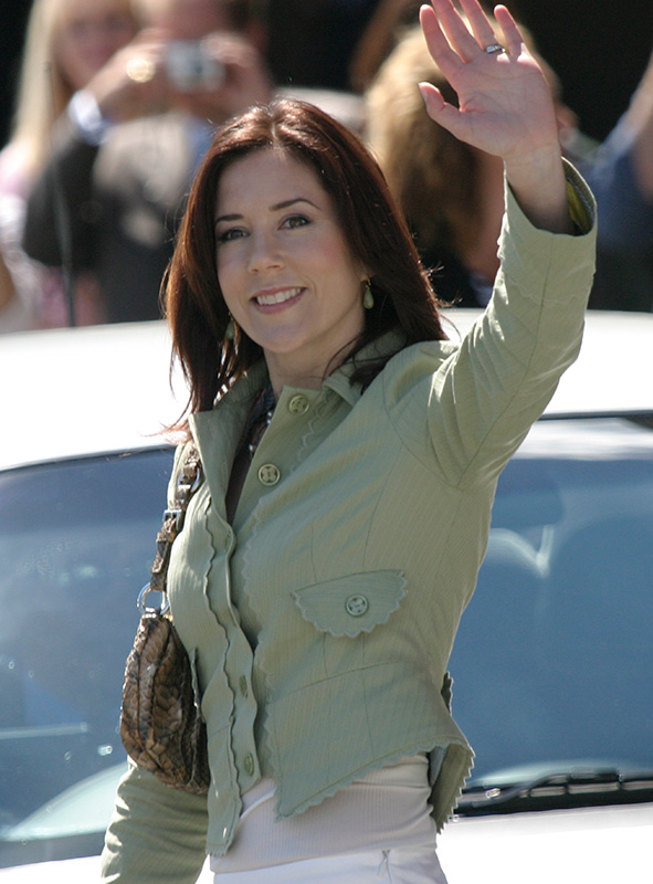 Mary Donaldson, wearing a fitted pale green jacket raises her left arm to wave. - click to view larger image