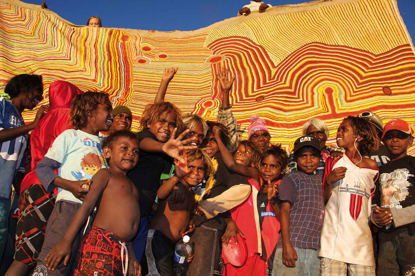 Martu Kids and artists in front of the painting Martumili Ngurra.