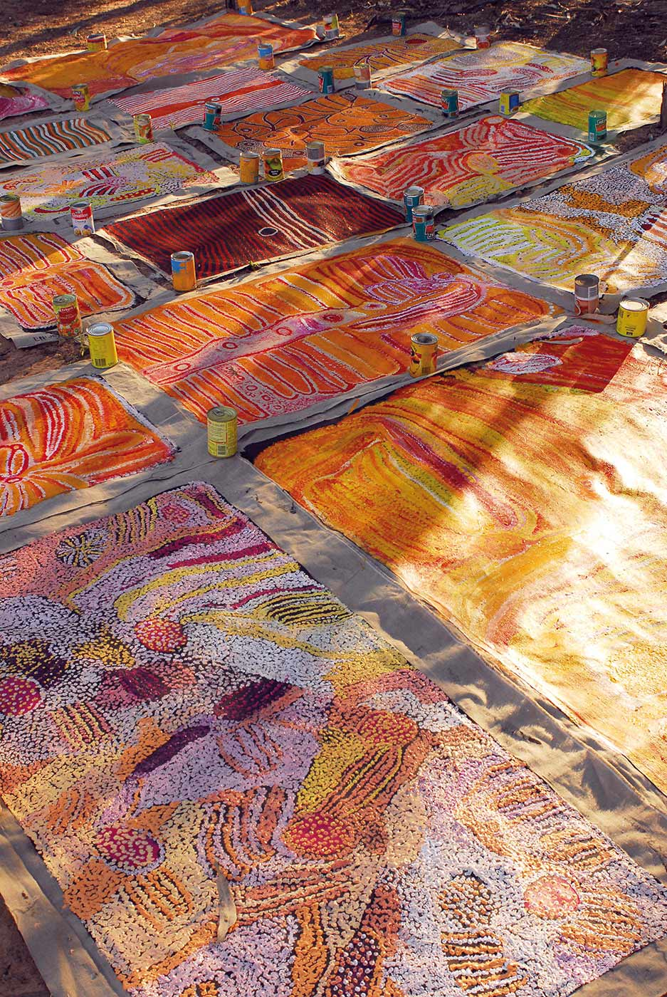 Colour photo of painting canvases spread out on the ground. There are tin cans placed on their edges in order to prevent them from blowing away. - click to view larger image