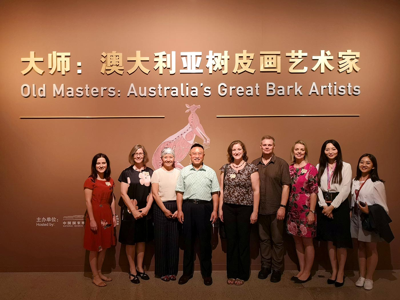 A group of people in front of a gallery wall with the title 'Old Masters: Australia's Great Bark Artists' beneath its Chinese translation.