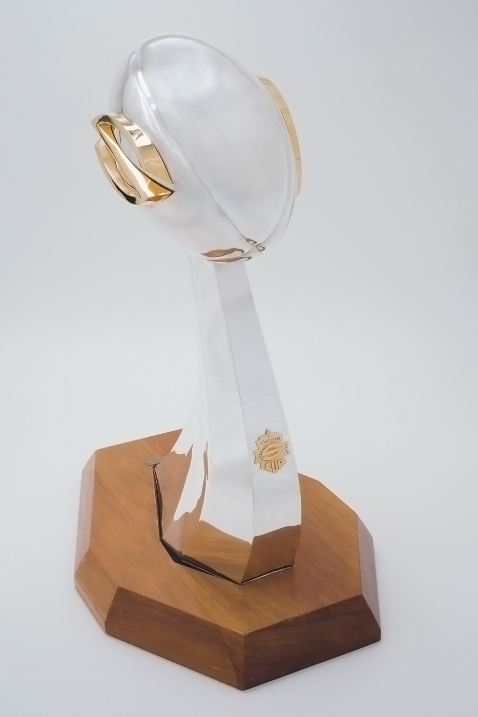 Trophy with a silver football extendeding above a wooden base. - click to view larger image