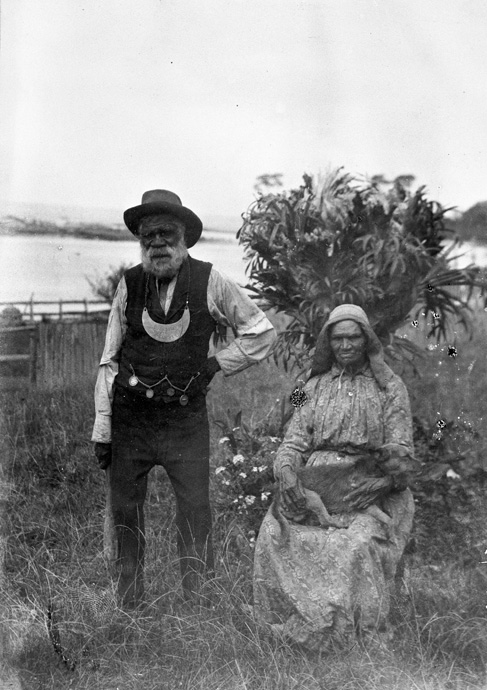 Black and white photo of a man standing and a woman sitting outdoors. The man is wearing a breastplate around his neck. - click to view larger image