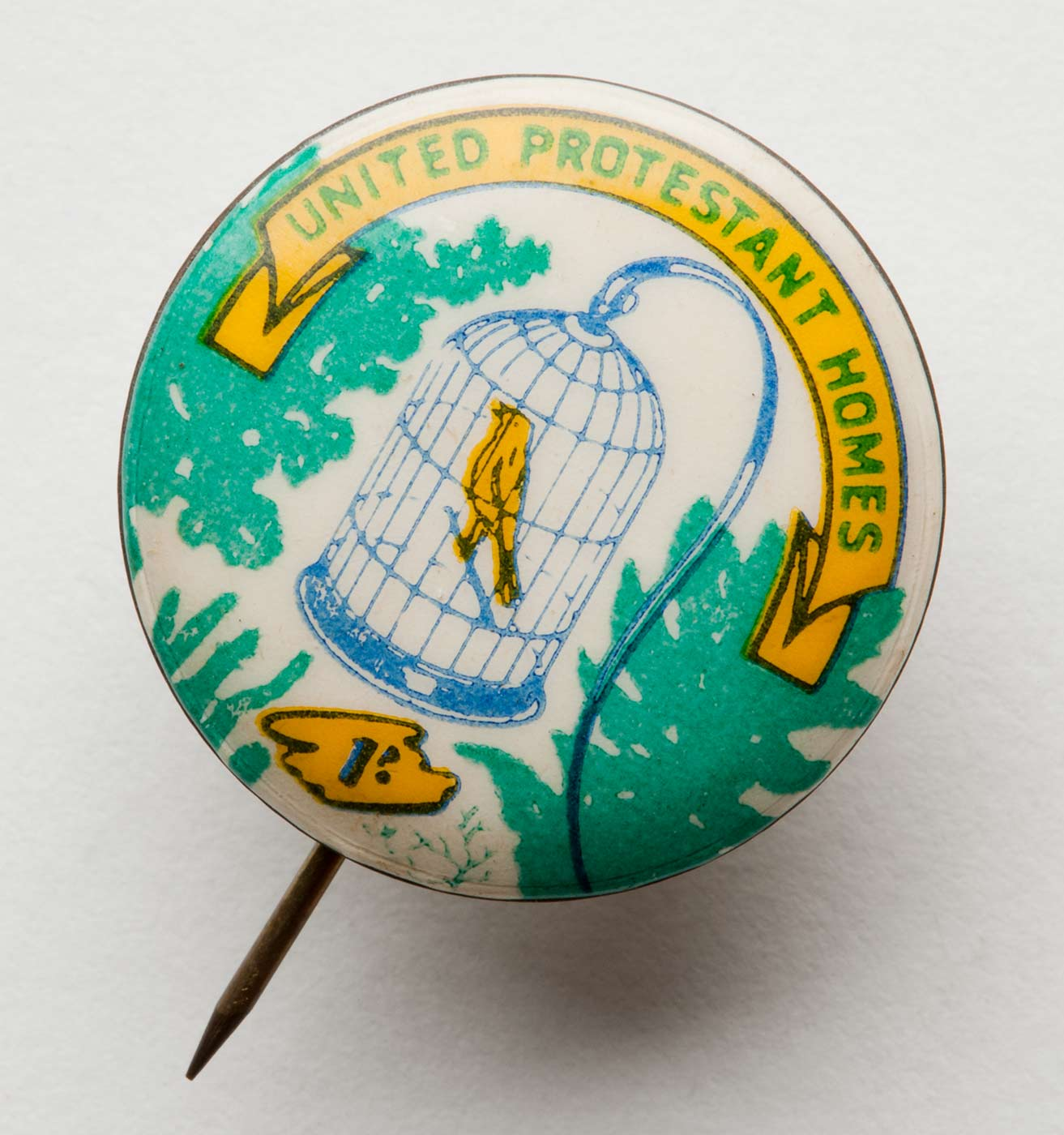 A metal circular badge with a white background showing a blue birdcage in the centre, containing a yellow bird. Green foliage is shown on either side of the birdcage. Text in green, printed on a yellow scroll above the cage, reads 'UNITED PROTESTANT HOMES'. - click to view larger image