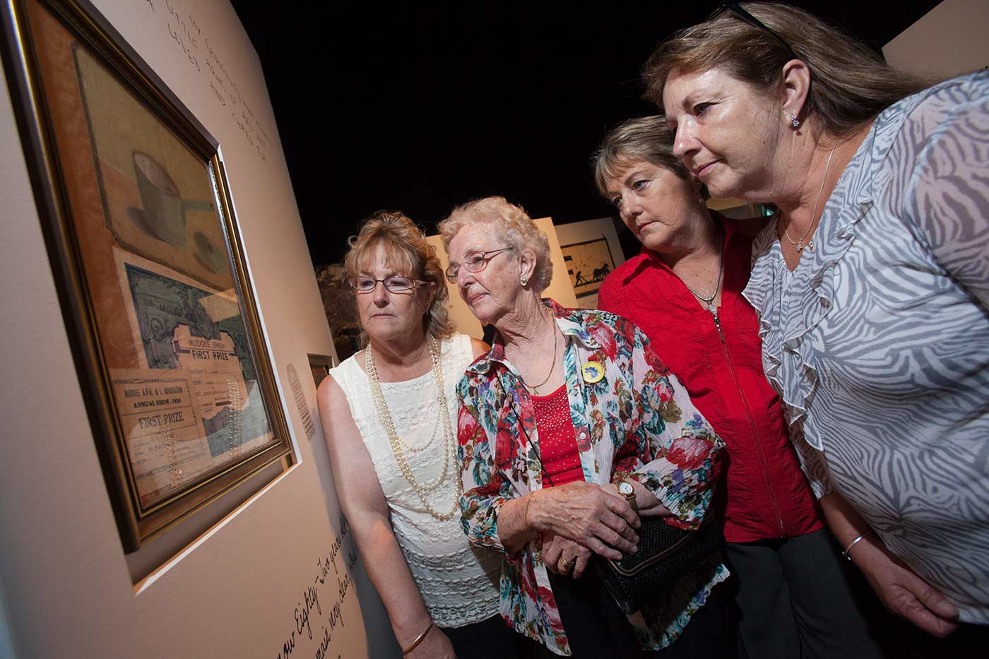 A colour photograph showing four women standing, looking at a display panel which includes a framed painting and two prize certificates. - click to view larger image