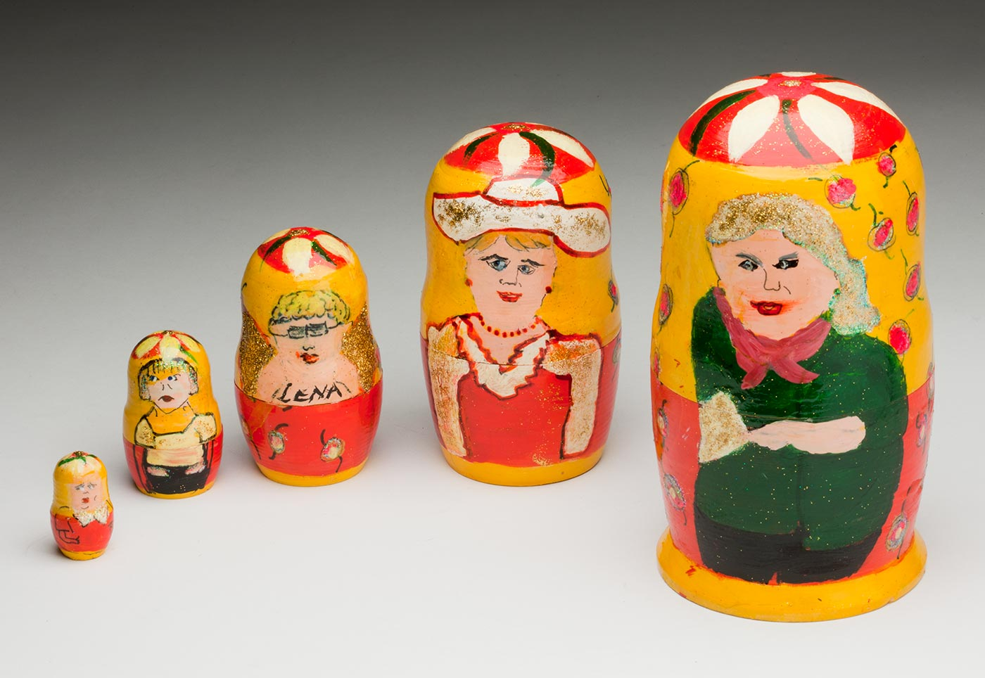 Five babushka dolls, arranged from smallest to largest from the left. Far left shows a small girl in a red top with white collar. Second from left shows an older girl wearing a white top and black pants. The third doll has short hair and glasses and 'LENA' handpainted on the chest. The fourth doll shows a woman wearing a red dress with white collar and hat, and the fifth shows a woman wearing a green shirt and red scarf. Gold glitter has been used to decorate the dolls. - click to view larger image