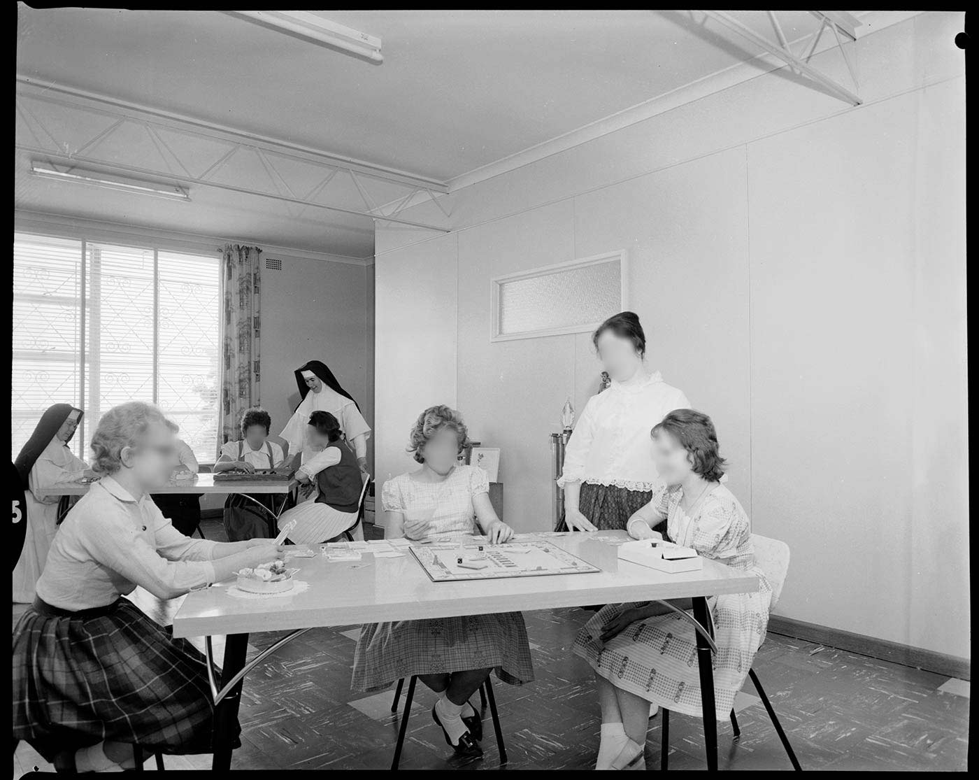 Black and white photo showing two groups of teenage girls sitting at tables, with a central gameboard. The girls' faces have been blurred. Two nuns are visible at the far table. - click to view larger image