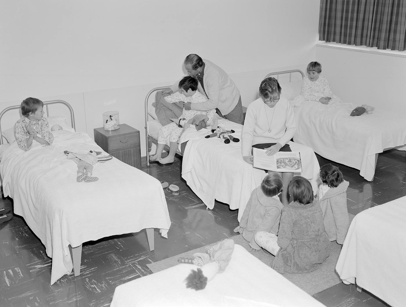 Black and white photograph of a ward with children in beds being attended to by staff. - click to view larger image