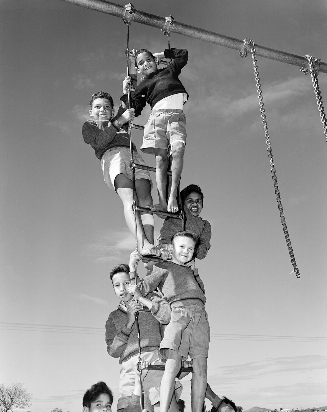 Black and white photograph showing a group of boys standing on a metal ladder in a playground. The boys wear school uniform of v-necked jumpers and shorts. The image clearly shows five smiling boys, with the heads of two other boys partially visible below. - click to view larger image