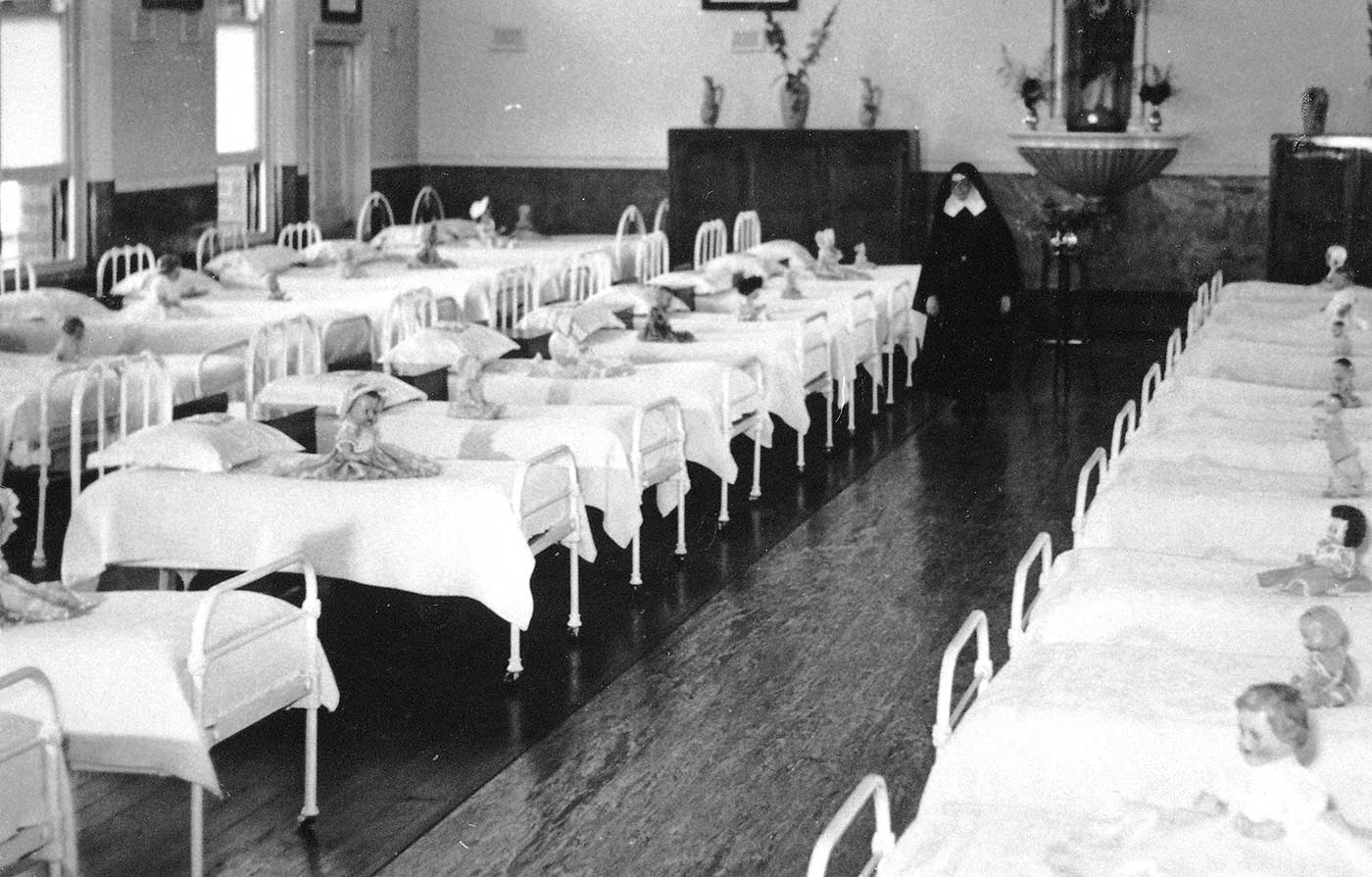 Black and white photograph showing three rows of small children's beds with white covers and a doll sitting on each. A nun walks down the centre of the room. - click to view larger image