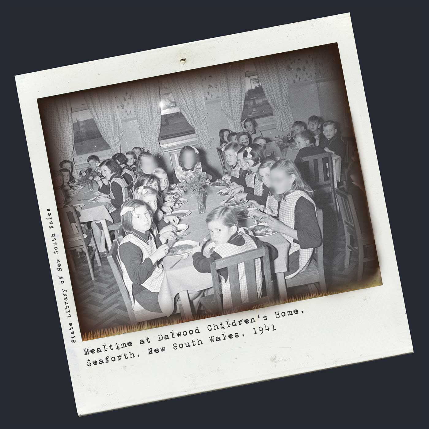 Polaroid photograph showing three tables of children sitting down to eat a meal. The girls wear black tops and checked aprons, and the boys wear dark suit coats. Each table has a vase of flowers at the centre. Typewritten text below reads 'Mealtime at Dalwood Children's Home, Seaforth, New South Wales, 1941'. 'State Library of New South Wales' is typed at the left side. - click to view larger image