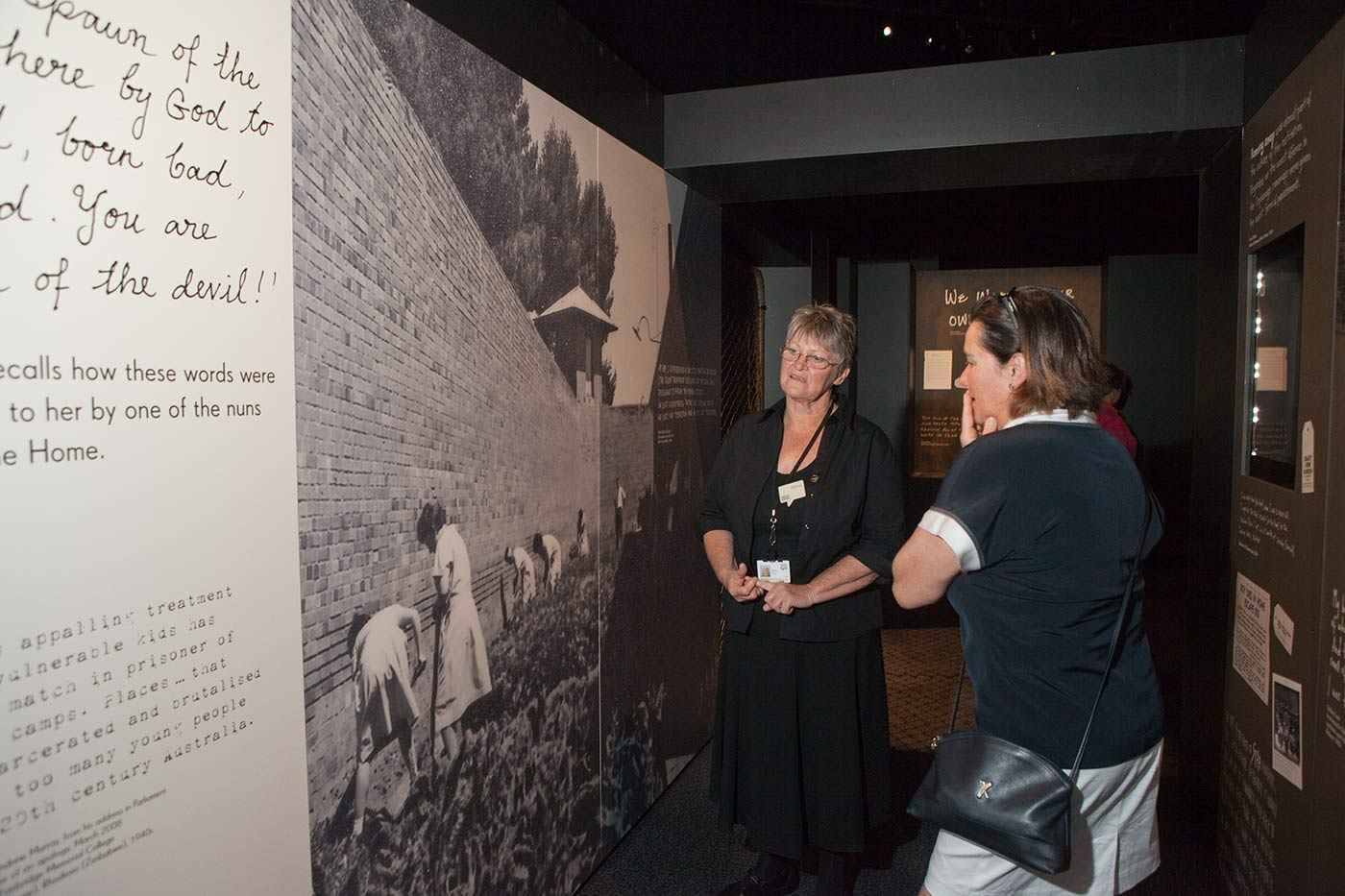 Colour photograph showing a woman standing in front of a large exhibition panel, talking to a visitor. The panel includes a black and white photograph of girls walking inside a brick wall. - click to view larger image