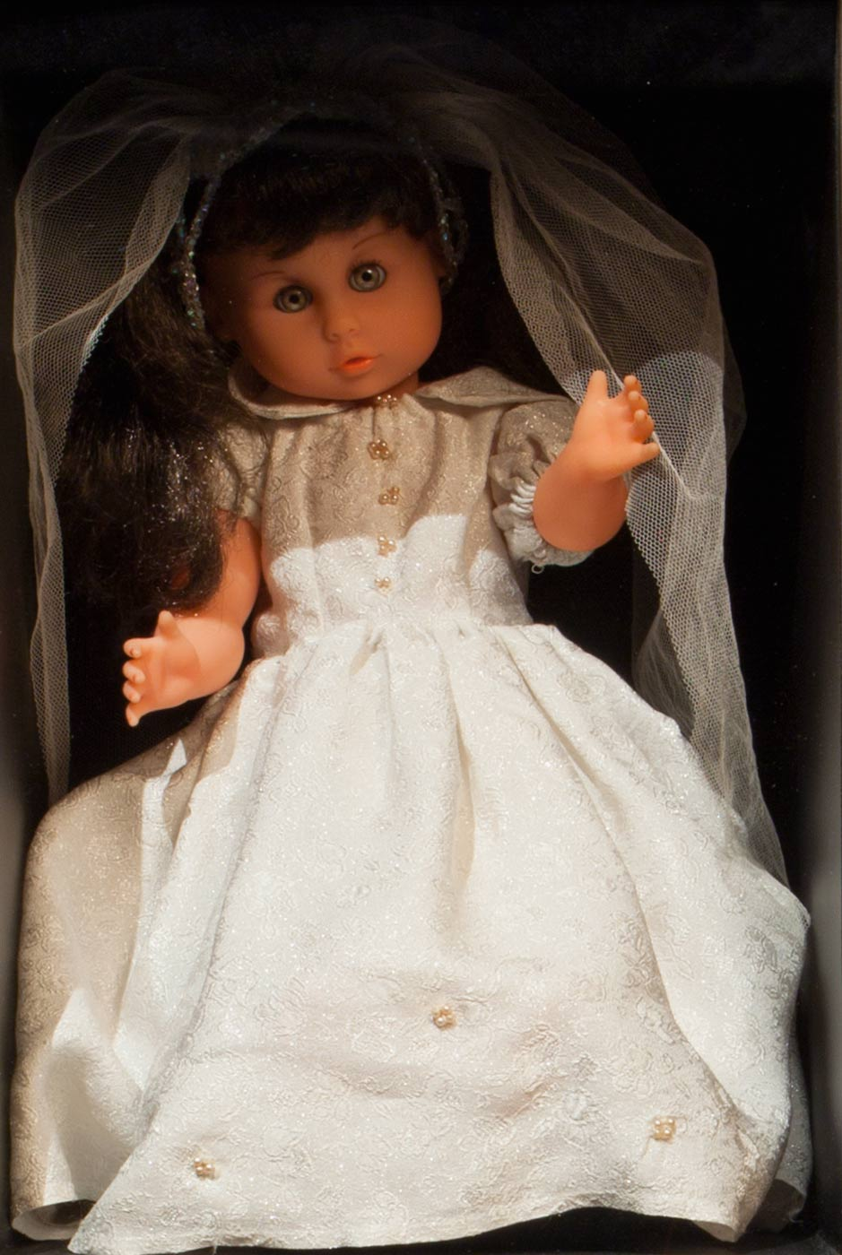 A colour photo of a dark haired doll wearing a bridal dress and veil. - click to view larger image