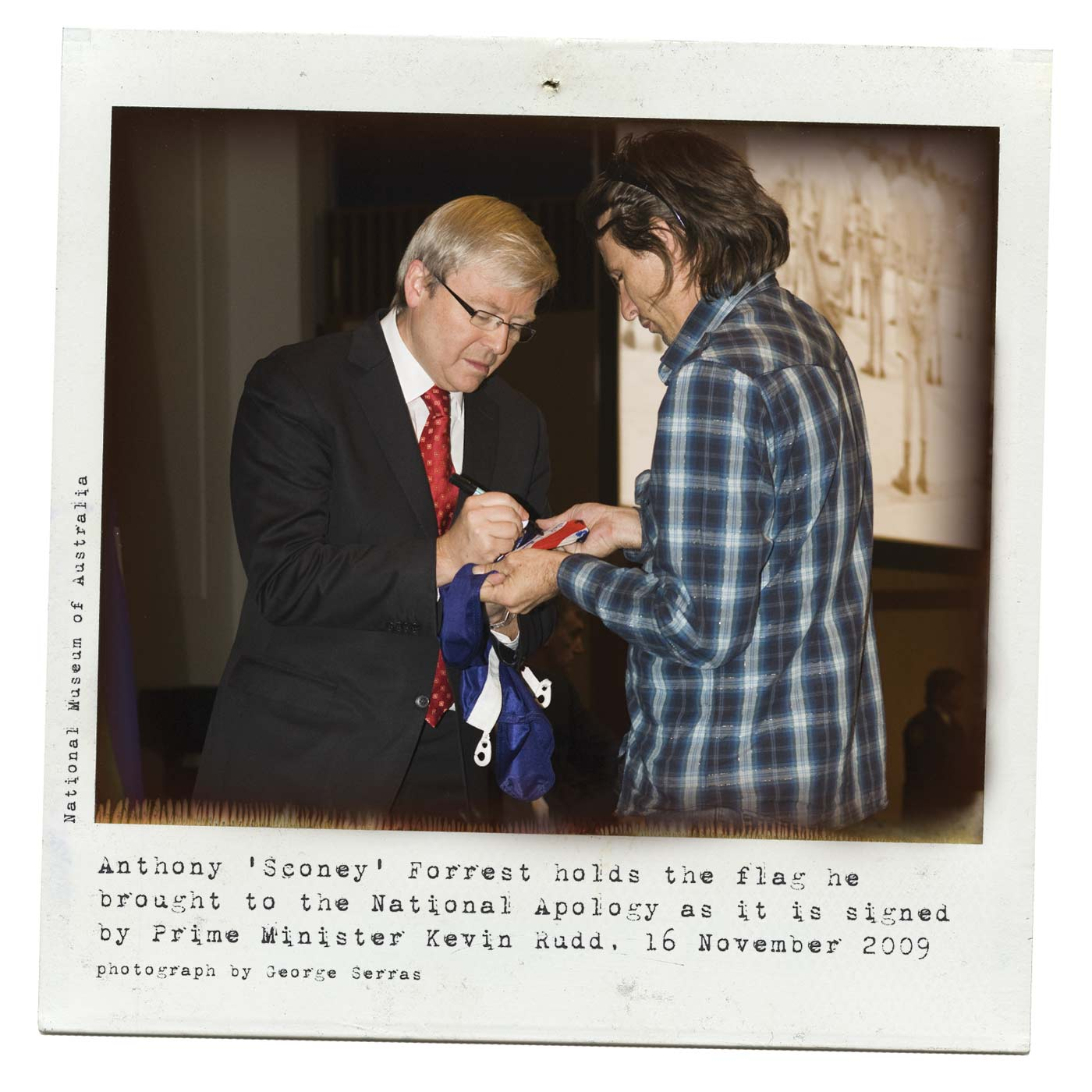 A Polaroid photo showing a side view of two men. A man in a suit, on the left, uses a texta to sign an Australian flag being held by the man on the right. Typewritten text at the bottom reads: 'Anthony 'Sconey' Forrest holds the flag he brought to the National Apology as it is signed by Prime Minister Kevin Rudd 16 November 2009. Photograph by George Serras'. - click to view larger image