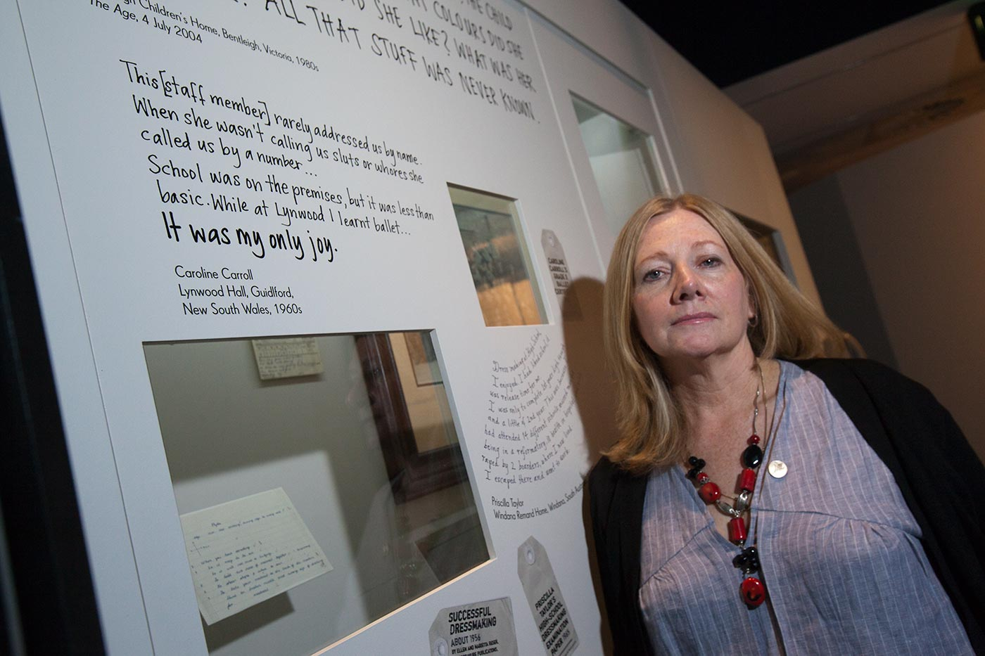 A woman stands beside an exhibition panel. - click to view larger image