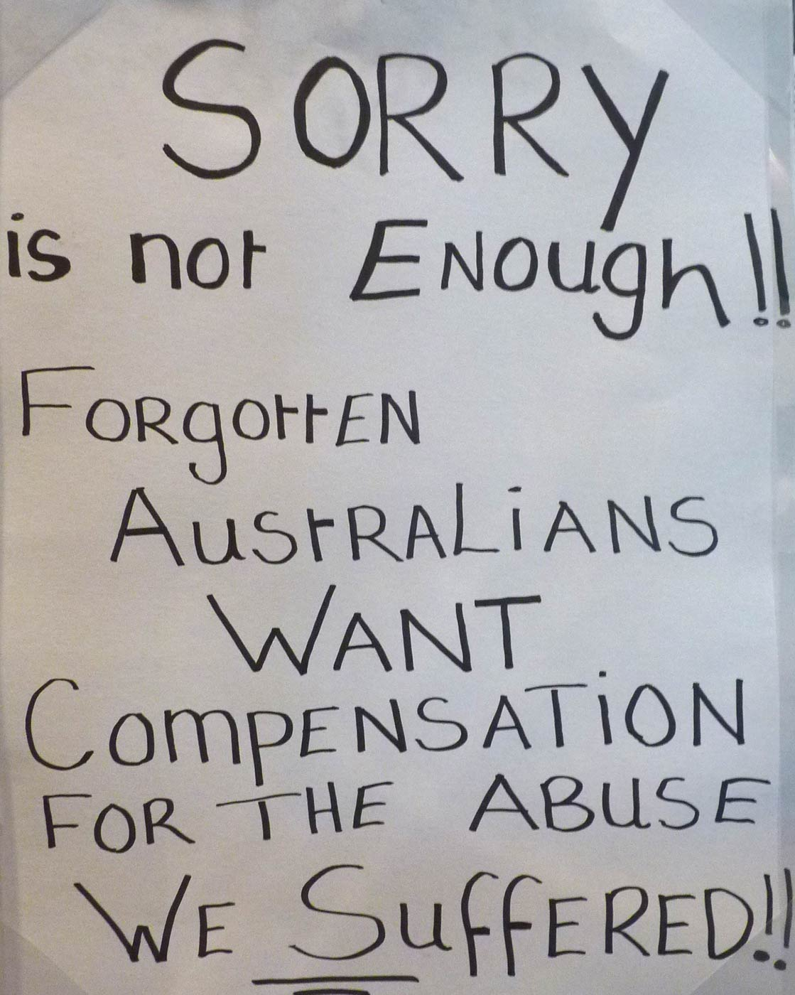 A protest placard of white cardboard with black handwritten text that reads, 'SORRY / is not Enough!! / FORgottEN / AustRaLiANS / WANT / CompENSATiON / FOR THE ABuSE / WE SuffERED!!'