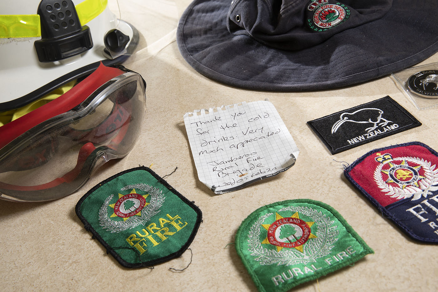 Cloth bages, a note, goggle and hat. The badges have embroidered text that reads 'Rural Fire', 'Fire' and 'New Zealand'.