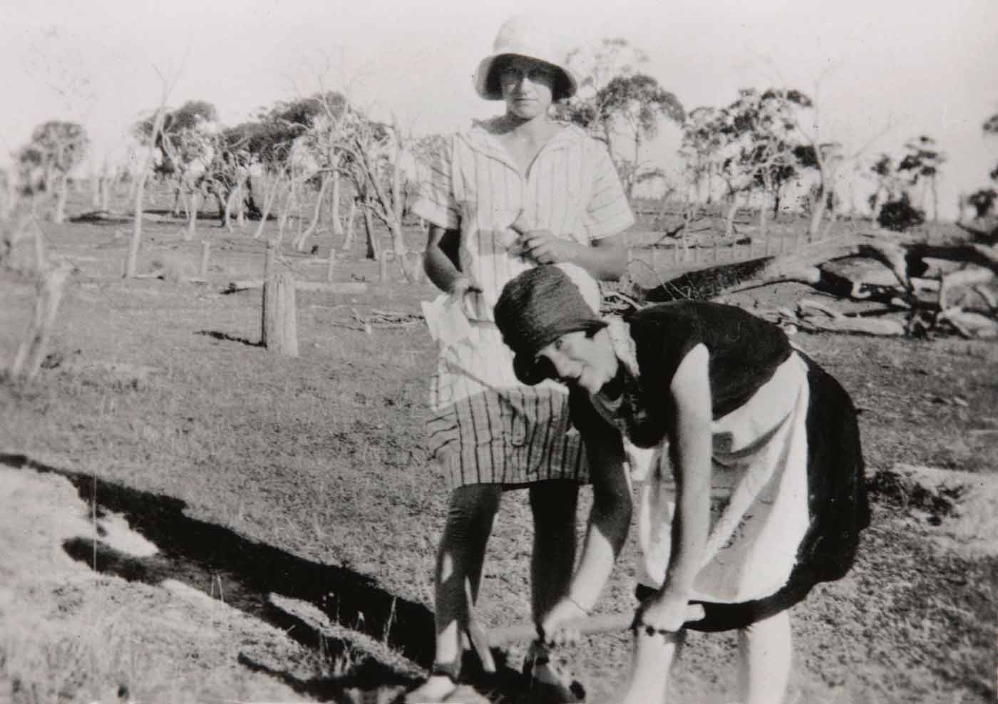 Photograph of a lady using a pick to dig out a rabbit burrow with another lady standing behind