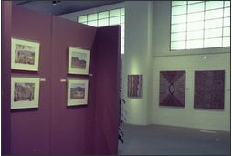 Photo of an exhibiton space showing four framed watercolour landscapes hanging on a maroon wall in the foreground. Three dot paintings hang on the white rear wall, with large windows above.