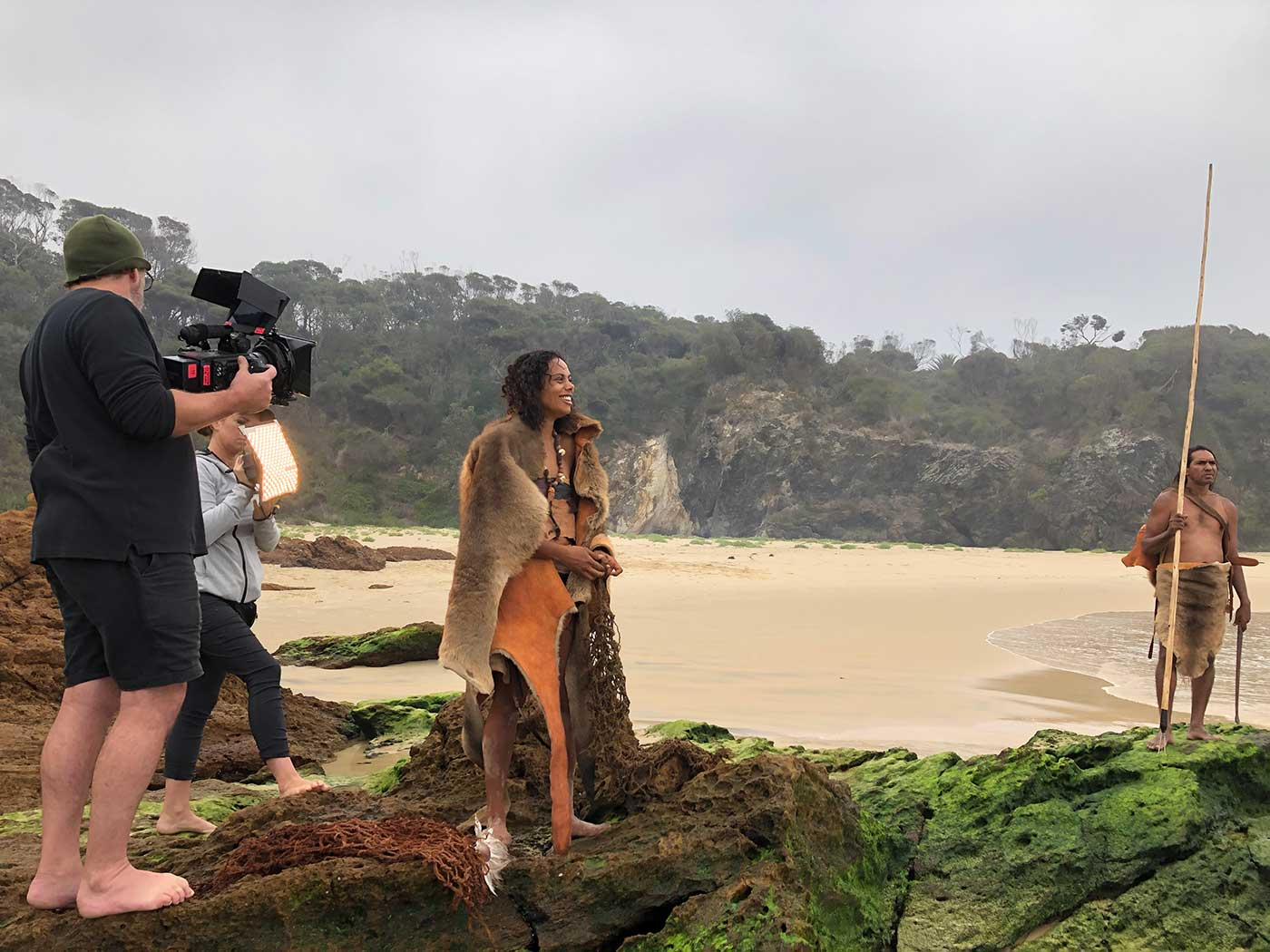 A female actor draped in animal skins stands on a beach with a film crew around her.
