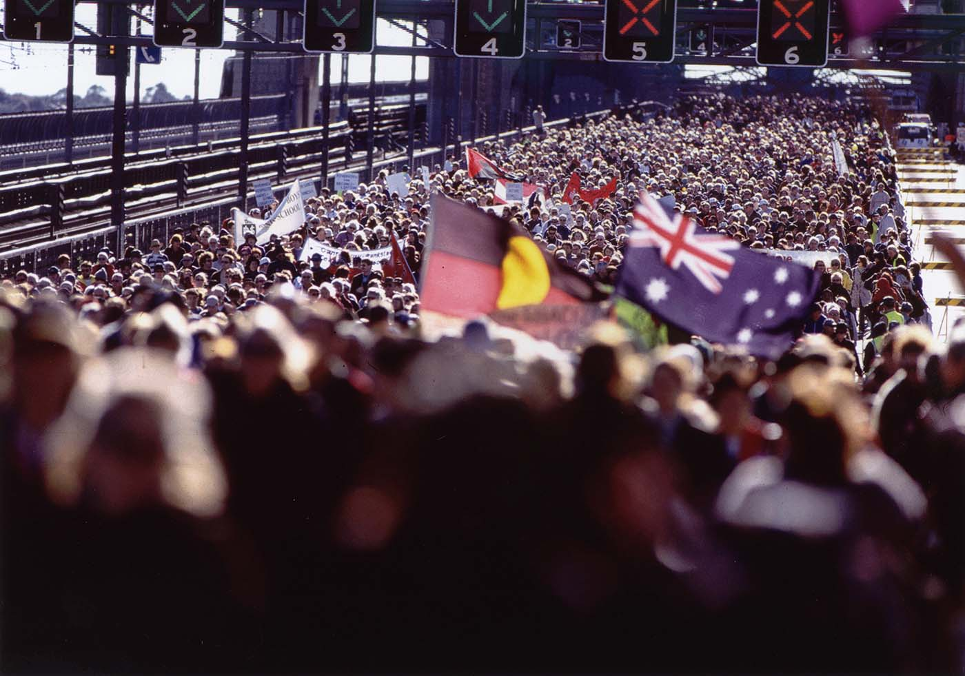 A vast crowd of people cover the roadway of the Bridge. People are carrying the Aboriginal and Australian flags. - click to view larger image