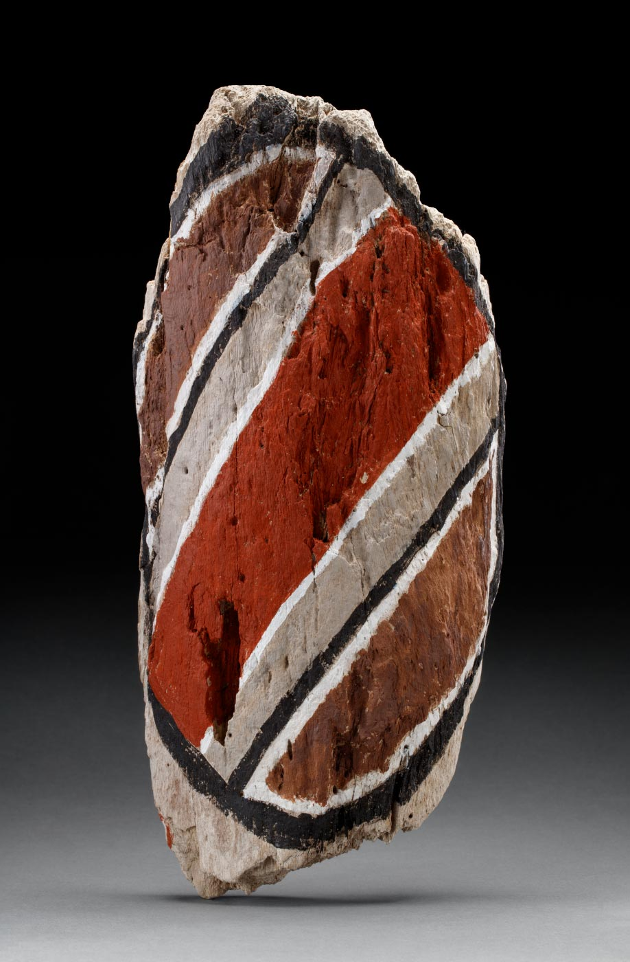 An acrylic painting on driftwood featuring a black oval line, with bands of orange and brown diagonal lines within it, which are also outlined with black and or white lines. - click to view larger image