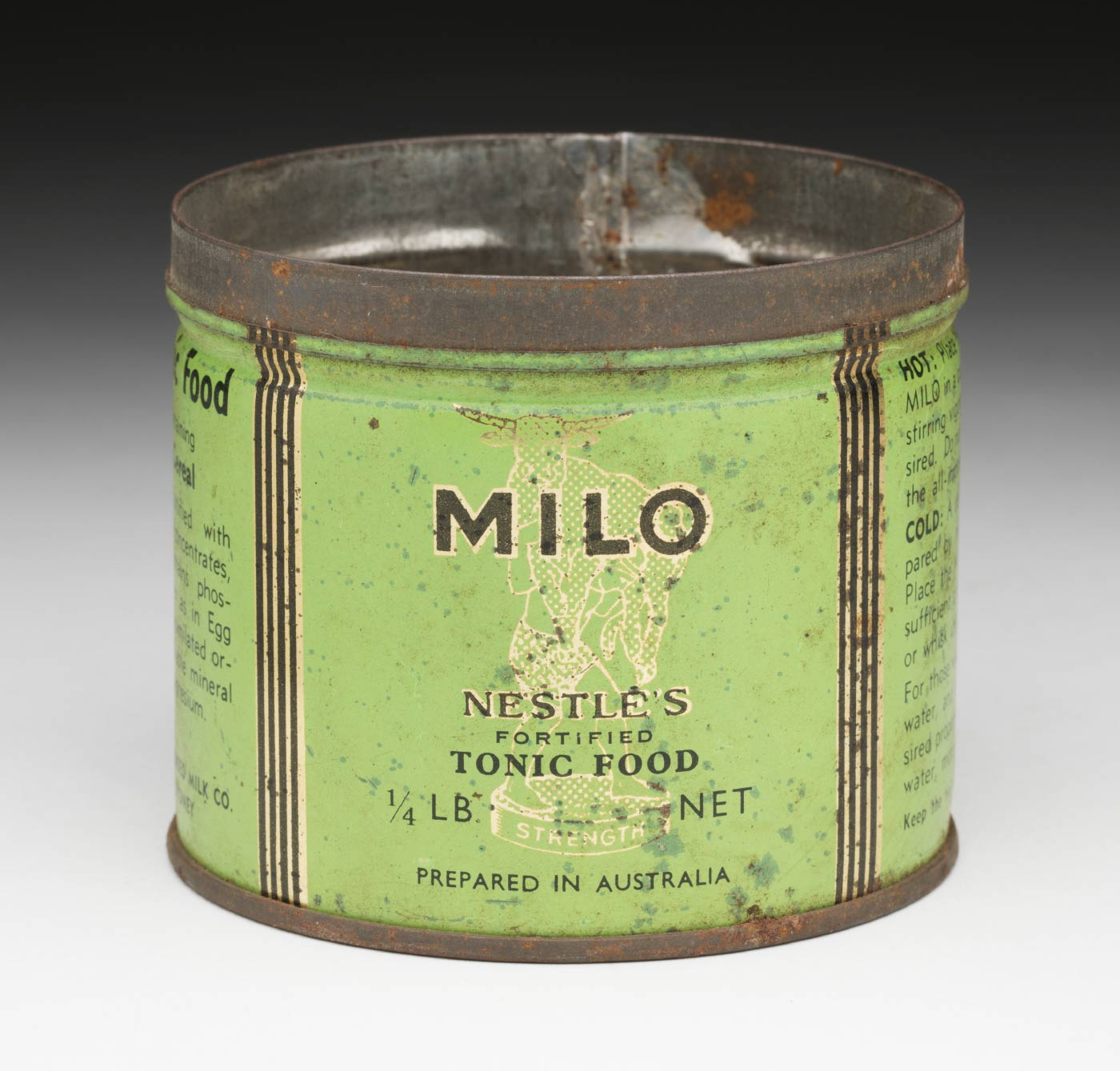 Round MILO tin without lid. The label is green, black and white and features an illustration of a bull being lifted by a man standing on a pedestal with the text 'STRENGTH' written on its side. on the label is the text 'MILO / NESTLE'S / FORTIFIED / TONIC FOOD / 1/4 LB NET / PREPARED IN AUSTRALIA'. - click to view larger image
