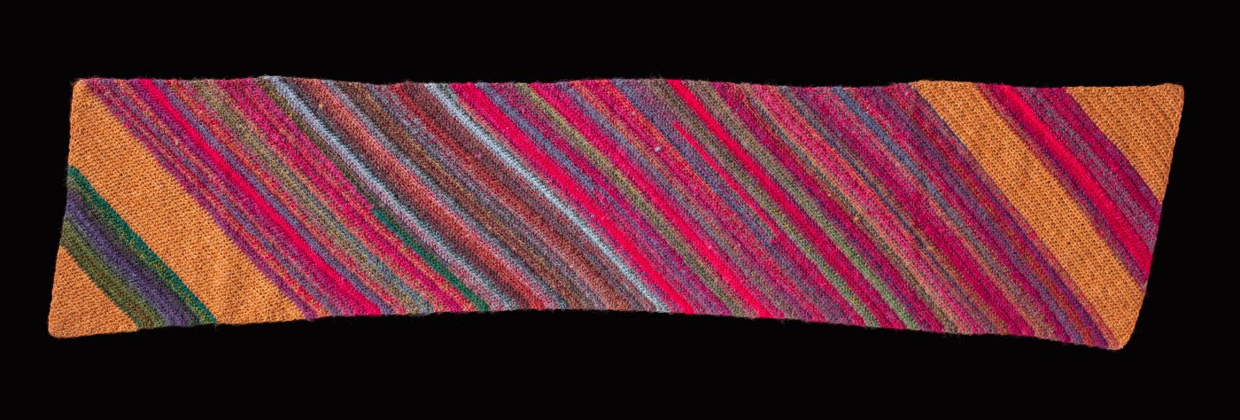 An oblong, striped hand-crocheted shawl made from a mixture of multi-coloured yarns. The main colours are gold-yellow and bright pink, with stripes of blue, green, grey, purple and white.