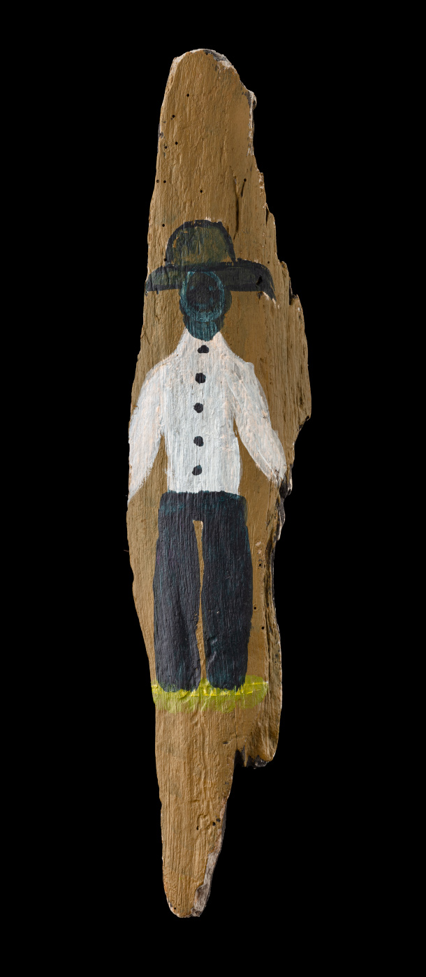 An acrylic painting on driftwood featuring a figure in black pants, white shirt with black buttons, a hat, and a combination of yellow/green shoes and grass at the feet. - click to view larger image