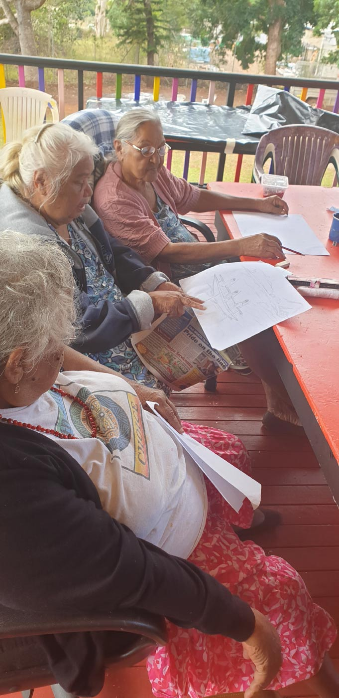 Colour photo of three elderly women sitting at a table and discussing an image of a boat carrying three people. - click to view larger image