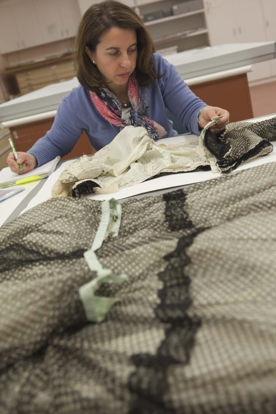 Conservator working on a dress and making notes. - click to view larger image