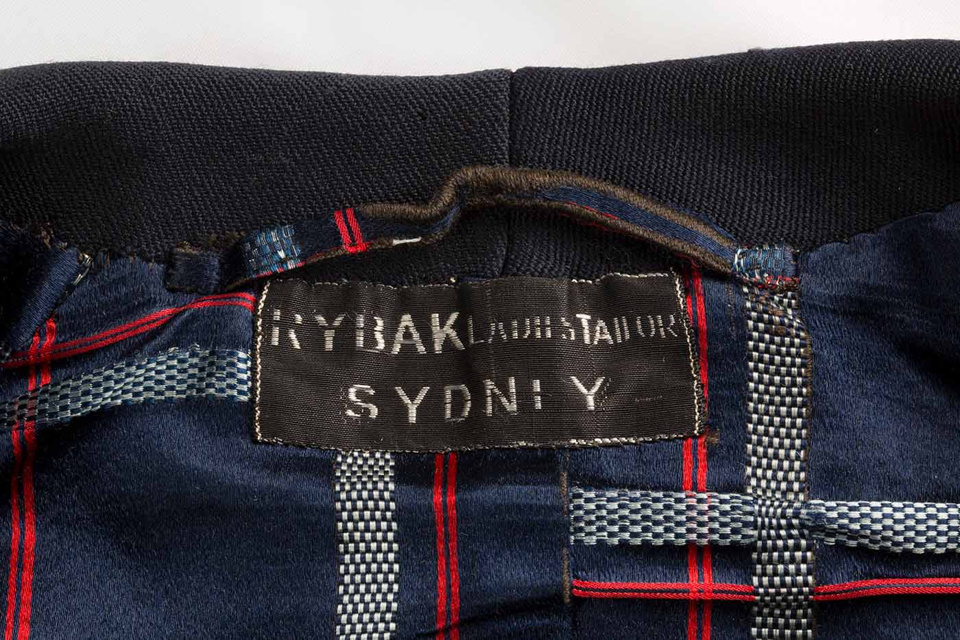 Navy, white and red checked satin lining of navy blue wool jacket with label that reads: 'RYBAK LADIES TAILOR / SYDNEY'.