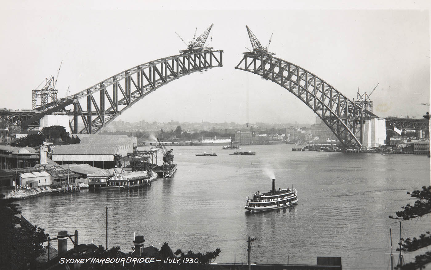 Photo taken from the north shore showing the two sides of the arch under construction. They have yet to meet. Large cranes are perched on top of each end of the spans. A ferry can be seen in the foreground. - click to view larger image