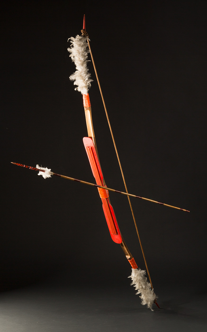 A bow and arrow set. The bow features a piece of wood with four cylindrical poles attached to the bowed wood and painted red. There are grey feathers attached to the ends bound with string also painted red. There is a thin piece of wood bound to the ends of the bowed wood with natural fibres. The arrow is attached to the bow with wire and features read bands the length of the shaft and red pigmented tip with carved twisted design and grey feathers attached. - click to view larger image